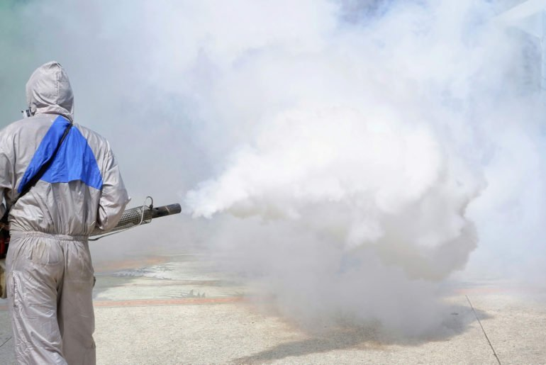 Worker using fogging machine spraying chemical to eliminate mosquitoes and prevent dengue fever